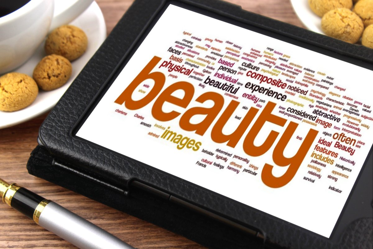 "A picture of a tablet with a large sized word ""beauty"" and different sized relevant words surrounded, such as images, ideal features, physical, and attractive."